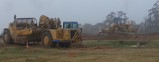 In the early morning fog, heavy equipment moves the earth making ready for a new neighborhood.